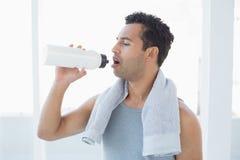 Homem com a toalha em torno da água potável do pescoço no estúdio da aptidão Foto de Stock Royalty Free