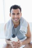 Homem com a toalha em torno do pescoço que guarda a garrafa de água no estúdio da aptidão Imagem de Stock Royalty Free