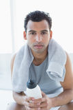 Homem com a toalha em torno do pescoço que guarda a garrafa de água no estúdio da aptidão Foto de Stock