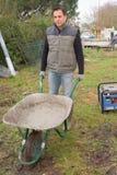 Homem com trabalho completo do cimento do carrinho de mão no jardim imagem de stock