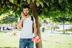 Homem com trouxa e um presente ao lado de uma árvore fotografia de stock