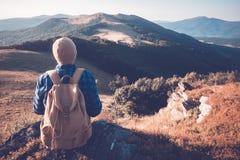Homem com a trouxa na estrada das montanhas fotos de stock royalty free