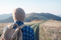 Homem com a trouxa na estrada das montanhas imagens de stock royalty free