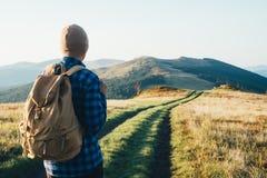 Homem com a trouxa na estrada das montanhas fotos de stock