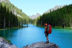 Homem com a trouxa pelo lago foto de stock royalty free