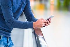 Homem com a trouxa que guarda o telefone celular no aeroporto fotos de stock