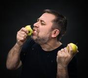 Homem com um apetite que come uma maçã verde imagem de stock royalty free