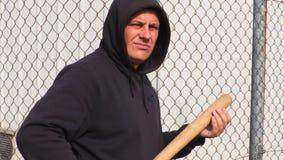 Homem com um bastão de beisebol perto da cerca vídeos de arquivo