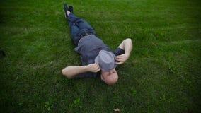 Homem com um chapéu que encontra-se na grama no parque vídeos de arquivo