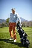 Homem com um clube e um saco de golfe Imagem de Stock