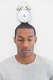 Homem com um despertador sobre sua cabeça Imagem de Stock