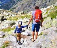 Homem com um filho nas montanhas Foto de Stock Royalty Free