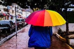 Homem com um guarda-chuva colorido que anda em uma rua chuvosa Foto de Stock