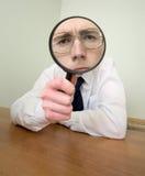 Homem com um magnifier em uma mão fotos de stock royalty free