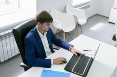 Homem com um portátil no escritório Fotos de Stock