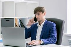 Homem com um portátil no escritório Imagem de Stock Royalty Free