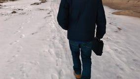 Homem com um saco do negócio que anda ao longo da costa ao longo da baía no inverno Vista traseira filme