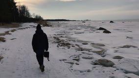 Homem com um saco do negócio que anda ao longo da costa ao longo da baía Vista traseira video estoque