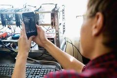 Homem com um telefone Na taxa de câmbio do bitcoin da tela fotos de stock