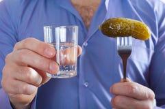 Homem com um vidro da vodca e de um pepino em uma forquilha em sua mão Imagens de Stock Royalty Free