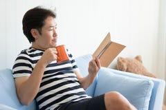 Homem com uma caneca e a leitura de um livro para relaxar foto de stock royalty free