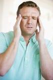 Homem com uma dor de cabeça Imagem de Stock