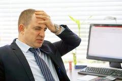 Homem com uma dor de cabeça na frente do computador fotos de stock royalty free