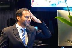 Homem com uma dor de cabeça na frente do computador imagem de stock royalty free
