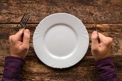 Homem com uma forquilha e faca em sua mão que espera sua refeição Imagens de Stock