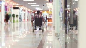 Homem com uma inabilidade em uma cadeira de rodas que vai à alameda vídeos de arquivo
