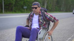 Homem com uma inabilidade em uma cadeira de rodas com uma trouxa que viaja na estrada Fim acima video estoque