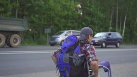 Homem com uma inabilidade em uma cadeira de rodas com uma trouxa que viaja na estrada Vista traseira video estoque