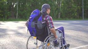 Homem com uma inabilidade em uma cadeira de rodas com uma trouxa que viaja na estrada Vista traseira Mo lento video estoque