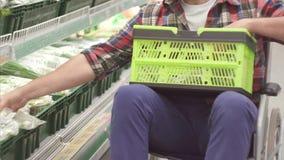 Homem com uma inabilidade em uma compra da cadeira de rodas no supermercado Tem uma cesta do alimento em seus joelhos Fim acima filme
