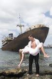 Homem com uma mulher nos braços perto de um navio abandonado Imagens de Stock Royalty Free