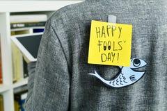 Homem com uma nota com o dia feliz dos tolos do texto unida a seus vagabundos Imagens de Stock Royalty Free
