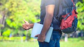 Homem com uma trouxa que está em um parque Mochileiro que guarda um portátil Conceito do nômada de Digitas foto de stock royalty free