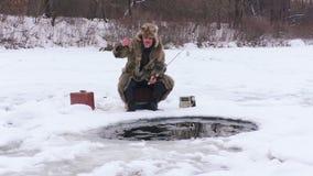 Homem com uma vara de pesca na pesca do inverno vídeos de arquivo