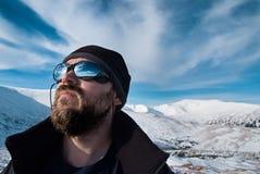 Homem com vidros e uma barba nas montanhas nevado Fotografia de Stock Royalty Free