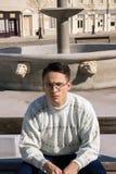 Homem com vidros na situação branca da camiseta no banco ao lado do founta foto de stock