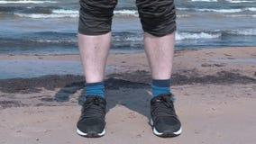 Homem com a volta acima da calças na praia perto do mar filme