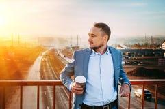 Homem com a xícara de café na ponte Amanhecer, o nascer do sol, a estrada desaparece na distância Foto de Stock Royalty Free