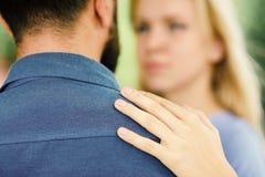 Homem como o apoio e a proteção para a mulher A menina abraça o homem farpado, pôs a mão sobre seu ombro fotografia de stock royalty free