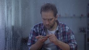 Homem comprimido que conta moedas atrás da janela chuvosa, rendimentos reduzidos, conceito da pobreza filme
