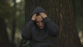 Homem comprimido que senta-se sob a árvore no parque, problema de desemprego, dificuldades filme