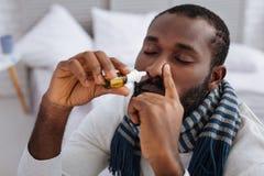 Homem concentrado calma que cura sua gripe em casa Fotos de Stock Royalty Free