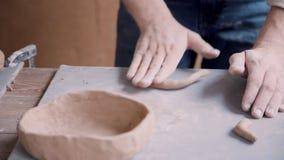 Homem concentrado do oleiro que molda a argila molhada no ofício e no studi acolhedor filme