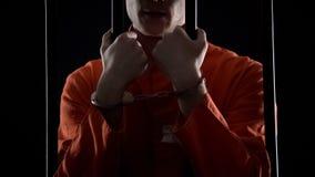 Homem condenado nas algemas que guardam as barras da prisão, punição para a fraude financeira imagens de stock royalty free