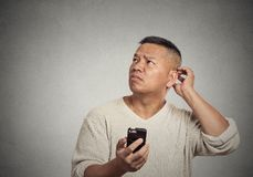 Homem confundido que olha acima de pensamento que responder à mensagem de texto recebida fotografia de stock royalty free