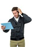 Homem confuso com tabuleta digital foto de stock royalty free